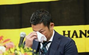 記者会見で涙をぬぐう阪神・岩田(1日)=代表撮影・共同