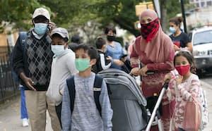 新型コロナ感染対策のためマスクを着けて登校する子どもと付き添いの保護者(ニューヨーク市、9月)=AP
