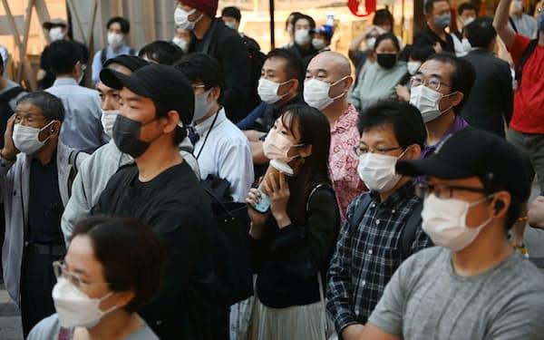衆院が解散され初の週末を迎え、街頭演説を聞く人たち(16日、東京都新宿区)