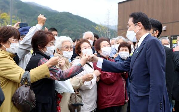岩手県大船渡市を訪れ、地元の人たちとグータッチする岸田首相(右端)=16日午後(代表撮影、共同)