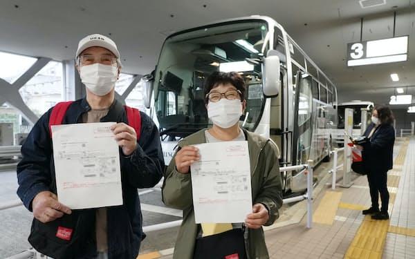 ワクチン接種証を手にバスツアーに参加する夫婦(17日、東京都町田市)=一部画像処理しています