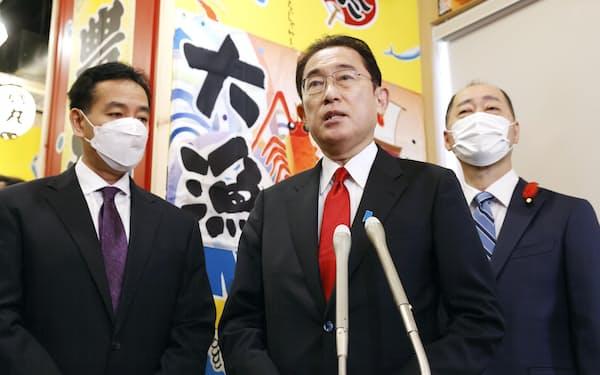 飲食店経営者らとの意見交換を終え、記者団の取材に応じる首相(中央)。左は山際経済再生相(18日午前、東京・新橋)=共同
