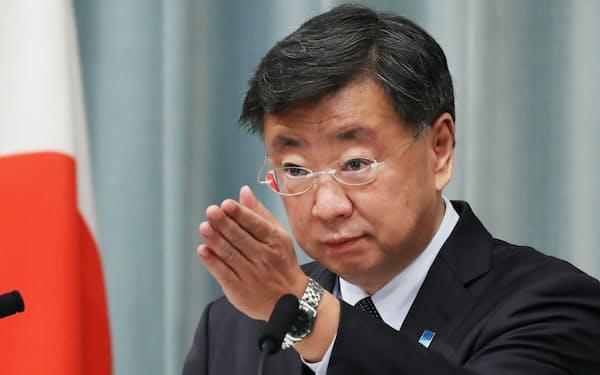 記者会見する松野官房長官(18日午前、首相官邸)
