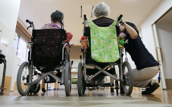 高齢化で医療・介護の負担はどんどん増えていく(特別養護老人ホームの入所者と介護職員)