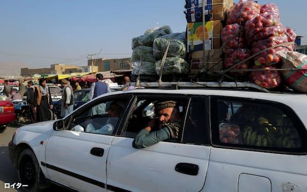 輸入減や通貨下落がアフガン経済に打撃を与える(18日、首都カブールの市場)=ロイター