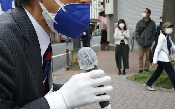 マイクカバーやマスク2枚をつけて街頭演説する候補者(19日、東京都内)
