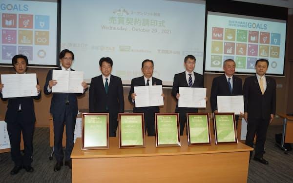 Jクレジットの売買契約の調印式を行った島根銀行の鈴木良夫頭取(右から4人目)ら関係者