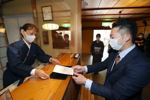 飲食店で「ワクチン・検査パッケージ」の技術実証が始まり、料亭「嵐山辨慶」の入店時にワクチン接種証を提示する利用客(21日午後、京都市右京区)=一部画像処理しています