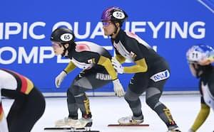 混合2000メートルリレー予選 吉永一貴(59)からタッチを受ける菊池純礼。準決勝進出を決めた(21日、北京・首都体育館)=共同