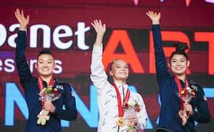 女子個人総合の表彰式で笑顔を見せる(左から)2位のリアン・ウォン、優勝のアンゲリナ・メルニコワ、3位のケーラ・ディセロ(21日、北九州市立総合体育館)=代表撮影・共同