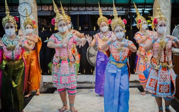 21日、タイ・バンコクでマスクを着けて踊るダンサー=ロイター