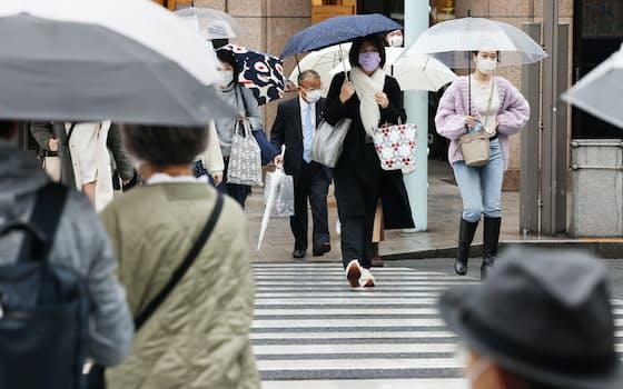 冷たい雨が降る中、東京・銀座を行き交う人たち。22日午前11時時点の気象庁の予報によると、東京の同日の最高気温は11度と、12月並みの寒さとなる見込み(22日午前)=井上容撮影