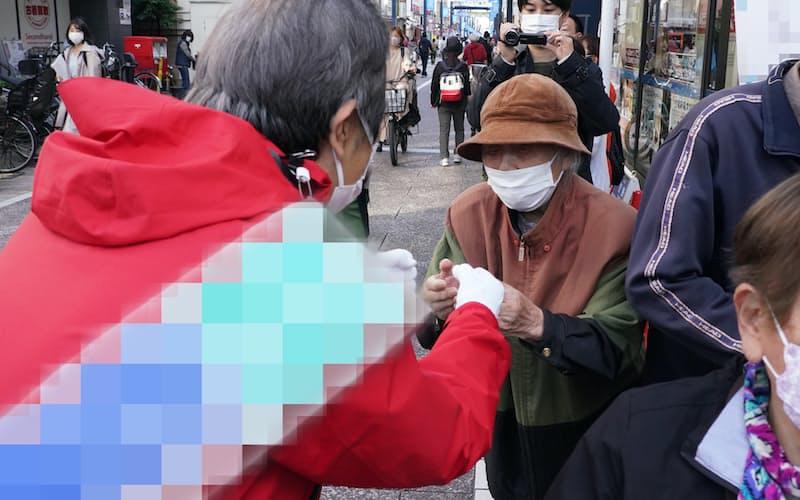 商店街を行き交う人に支持を訴える候補者(24日、東京都内)=一部画像処理しています