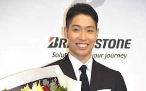 記者会見で現役引退を発表し、花束を手に笑顔の競泳男子の萩野公介(24日、東京都内)=共同