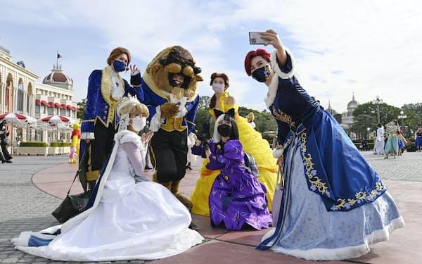 東京ディズニーランドでハロウィーンの仮装をして記念撮影する人たち(25日午前、千葉県浦安市)=共同