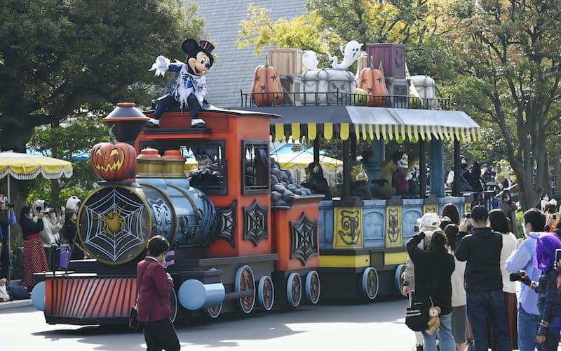 ハロウィーンの特別プログラムが開催された東京ディズニーランドで、パレードを楽しむ人たち(25日、千葉県浦安市)=共同