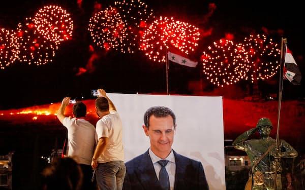 アサド大統領のポスターの近くで、同氏の4選を祝う支持者ら(5月、ダマスカス)=ロイター
