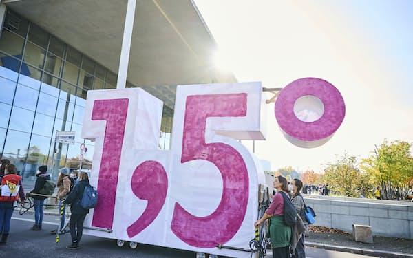 「1.5度目標」の実現を訴えベルリンでデモ行進する市民団体など(10月24日)=AP