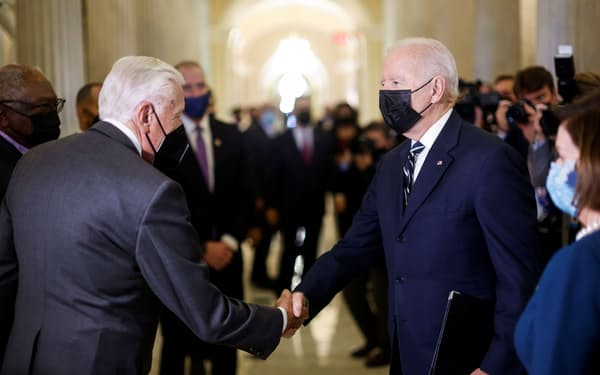 バイデン米大統領(右)は民主党議員に看板政策の実現へ協力を求めた(28日、ワシントン)=ロイター