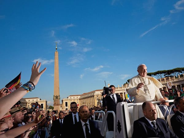 歓喜に沸く群衆のなかを、オープンカー型の教皇専用車で通り抜ける。サンピエトロ広場で行われる水曜恒例の一般謁見で。(Photo by Dave Yoder/National Geographic)