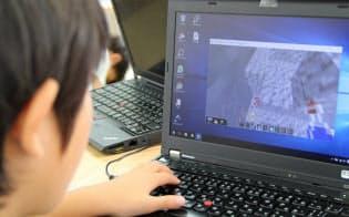子供たちはマインクラフトでプログラミングを学ぶ(写真上、さいたま市)。作ったプログラムが自動でブロックを積む(同下)