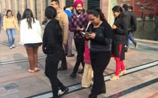 インドの都市部ではスマホをいじりながら歩く若者の姿が目立つ(デリー)