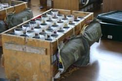 配線までが完了した状態の筒。箱の手前側の袋にくるまれたものが点火装置。1台の点火装置で16本の筒に点火できる