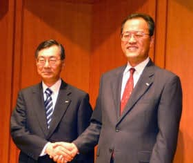 写真1 KDDIの小野寺正・社長兼会長(左)と12月1日付けで新社長に就任する田中孝司・代表取締役執行役員専務(右)