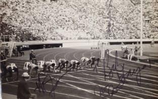 東京五輪100m走のスタートの様子。金メダルをとったボブ・ヘイズ氏(右下)、銀メダルのヒュゲロラ氏(左下)、スターターの佐々木氏(右上)のサインが入っている。紙焼きを筆者が撮影。写真提供は野崎忠信明星大学名誉教授、野崎忠信「1964年東京オリンピック大会コレクションと資料」所収