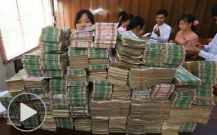 マイクロファイナンス機関「ソシオ・ライト・ファウンデーション」の事務所に積まれた約6000万チャット(約500万円)の札束。このうち半分が一日の融資額となる(ヤンゴン郊外)