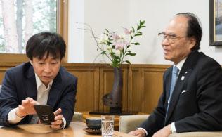 青野社長(左)はスマホで写真に撮って持ち歩いている記事を塚越会長に見せた