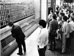 ブラックマンデーの影響で暴落した株価ボードを見つめる人たち
