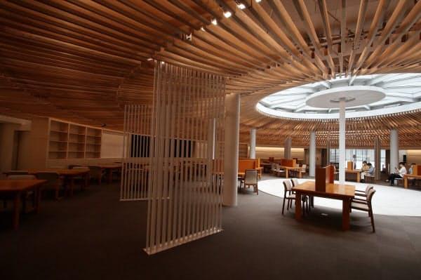 地下1 階のライブラリープラザ。天井には、国産スギのルーバーを放射状に配した。写真手前にある縦格子のパネルは、冷温水による輻射空調。床染み出し空調と併用した。総合図書館の改修工事中は同館の学習室の機能をライブラリープラザが補う。改修工事終了後には、交流拠点として使用する計画だ(写真:日経アーキテクチュア)