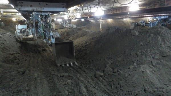 気圧が高まるにつれ、人が作業できる時間が短くなることから、地下25mよりも深い地点での掘削作業は、ショベルカーを遠隔操作して無人で行った(写真:清水建設)