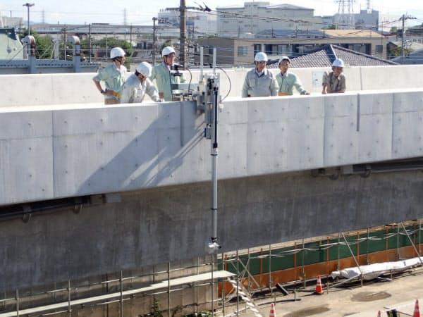 神奈川県内の橋の建設現場で実証実験している様子。高欄に設置しているのが自走式のロボットカメラ(写真:三井住友建設)