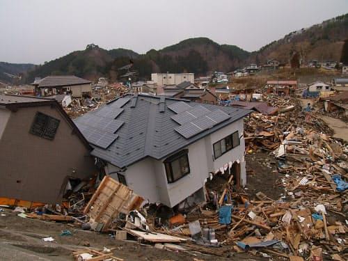 津波で流された木造住宅が、引き波で戻されたのか防潮堤に張り付いて止まっている(写真:日経コンストラクション)