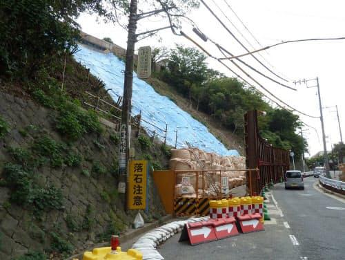 沿道からの「もらい事故」の例。2014年に神奈川県横須賀市の市道脇の斜面が大雨で崩落。土砂が反対側の駐車場まで流れ出て車両2台が被害を受けた。市は斜面が民有地であることから有効な対策工事を実施できなかった(写真:日経コンストラクション)