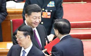 全人代の閉幕式を終え、張徳江・全人代前委員長(右)と握手する習近平国家主席(20日、北京の人民大会堂)=三村幸作撮影