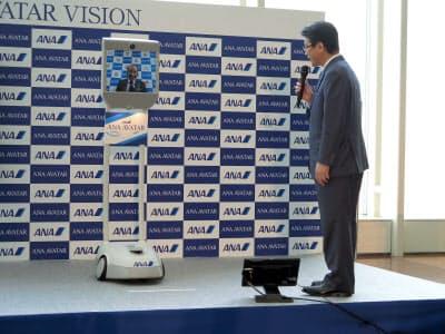 説明会ではANAHDの片野坂真哉社長(右)が、自走式のテレビ会議装置「Beam Pro」の画面越しに大分県の広瀬勝貞知事と会話した