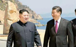 北朝鮮の労働新聞が9日掲載した、中国遼寧省大連の浜辺を歩く金正恩朝鮮労働党委員長(左)と習近平国家主席の写真=コリアメディア提供・共同