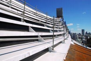 国立代々木競技場・第一体育館の大屋根(南面)で進む塗装工事。白く見える部分に錆止めなどを塗っている。傾斜が急な塔屋付近では、屋根に張り付くように足場を組んだ。3月4日に撮影した (写真:日経アーキテクチュア)