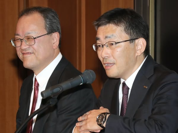 KDDIの社長に就任する高橋副社長(右)と会長に就任する田中社長(1月、都内)