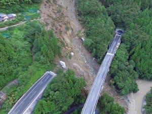 左の上り線の橋桁が流失し、2本の橋脚が斜面上に残る。その先に見えるのは全長780mの立川トンネルの南側坑口。崩れた土砂が坑口の大半を塞いでいる(写真:都築安和)