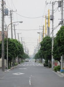 住宅街の道路に並ぶ電柱。左手側奥の電柱が傾いているのがわかる(写真:日経ホームビルダー、2011年7月28日撮影)