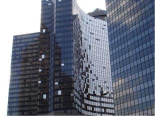 2005年8月に来襲したハリケーン「カトリーナ」でガラスが割れた、米国ニューオリンズ市内の高級ホテル「ハイアット・リージェンシー」の高層ビル。写真中央の白い部分はすべて、割れたガラスを応急的にふさいだ箇所(写真:日本建築総合試験所)