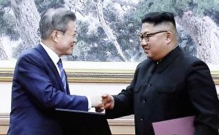 合意文書に署名し、握手する文在寅大統領(左)と金正恩委員長(19日)=聯合・共同