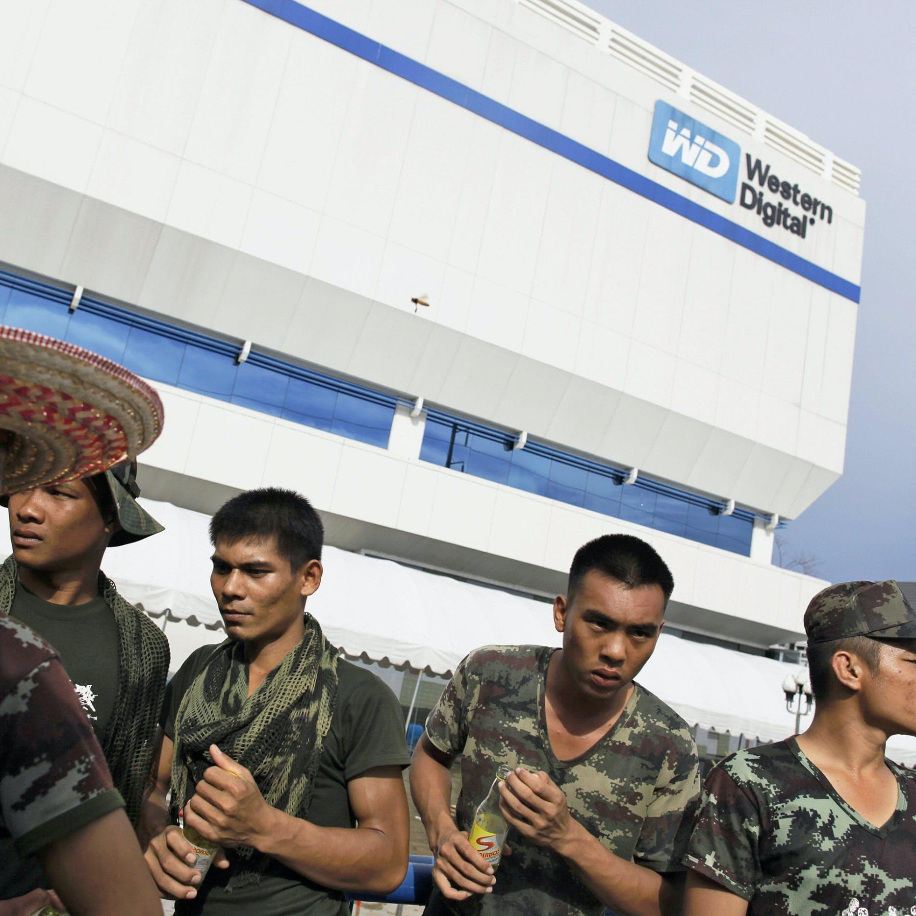 ウエスタン・デジタルの工場も被災した(10月中旬、アユタヤ県で救援中に休息をとる兵士)=ロイター