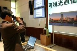 双眼鏡にイメージセンサー受光器を取り付けた試作機(16日、慶応義塾大学でのデモ)