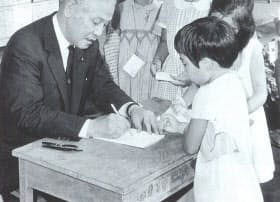 ラジオ体操会で子供にサインする灘尾文相