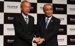 握手する富士フイルムHDの依田章執行役員(左)と長崎県の中村法道知事